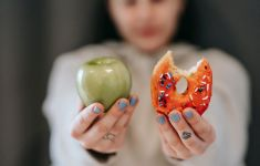 Woman holding up a green apple and a donut with a bite out of it.