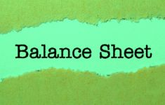 Green torn paper with typed words BALANCE SHEET