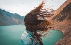 Woman's hair blowing in the wind near a lake.