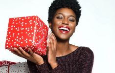 Happy woman holding a boxed gift.