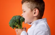 A child bites into head of broccoli in front of orange background.