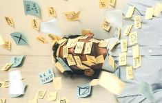 Man laying on floor covered in Post-it notes