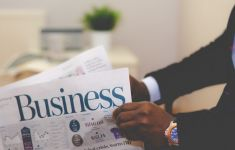 man's hands holding business section of newspaper