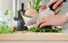 Close up of woman's hands chopping herbs in kitchen