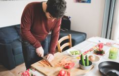 Man chopping vegetables on his kitchen table