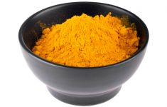 Black ceramic bowl filled with powdered turmeric