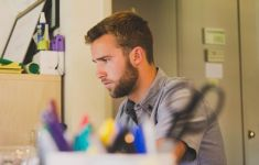 young bearded man focused on work in office