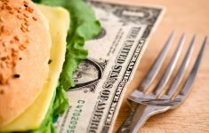 Dollar bill tucked into cheese sandwich next to fork