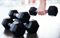 Hand picking up weighted dumbbell from stack.
