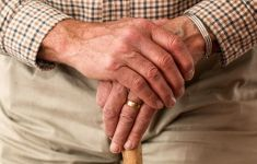 Elderly man's hands folded over handle of cane walking stick