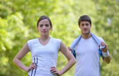 Woman and man in white t shirts outside exercising.