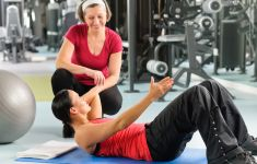 Personal trainer overseeing woman doing situps
