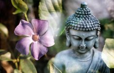 Buddha statue in garden with flower
