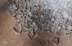 Broken glass pieces strewn in dirt.