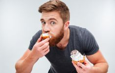 Bearded man looking guilty as he eats cake