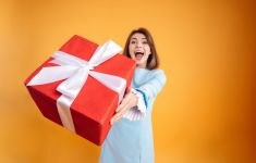 Happy woman in front of orange background presenting big red gift