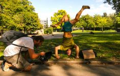 man in park doing headstand with photographer nearby