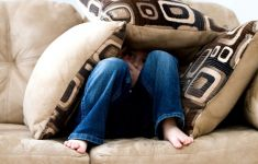 Woman hiding in fort of couch cushions.