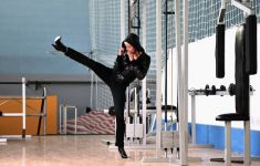 WOman in black hoodie takes kickboxing high kick stance