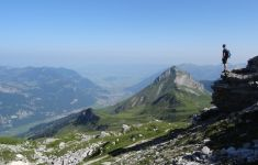hiker looking from rock across valley