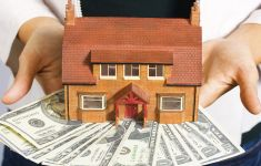 Person holding small model house with money in hands