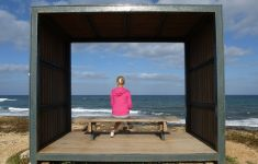 View from behind woman sitting on bench inside box gazing at the ocean.