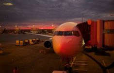 nose of airplane as it is being loaded at sunset