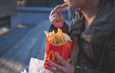 Close up of woman eating McDonalds French fries outdoors.