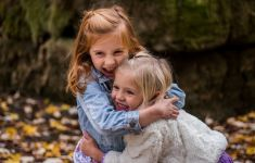 Two girls hug among autumn leaves.