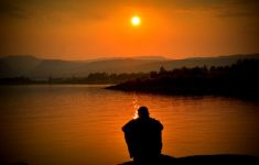 Silhouette of man sitting alone by a sunset lake.