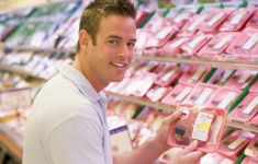 Man at butcher shelf full of meat in grocery store.