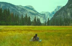 couple sitting in field looking at mountains