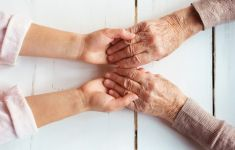 Close of of elder person's hands holding a child's hands on white table.