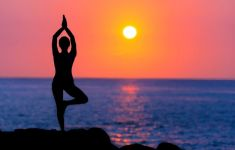 Woman on beach in silhouette practicing yoga at sunset