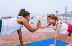 Two exercizing women high five each other while doing plank pose.