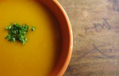 Orange bowl of pumpkin soup on wooden table.