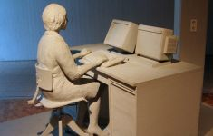 Clay sculpture of woman sitting and desk with computer.