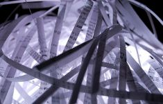 close up of typed paper gone through shredder