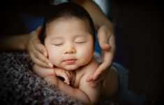 Infant asleep with mother's hands around her face