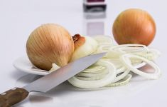 sliced and whole onions on plate with kitchen knife