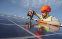 Man in hardhat with drill installing solar panel