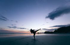 Sunset silhouette of woman doing high kick exercise on beach