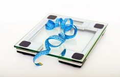 blue tape measure atop glass bathroom scale