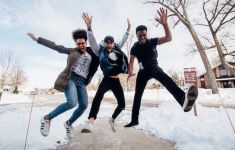 Three teenage boys jumping on a snowy sidewalk