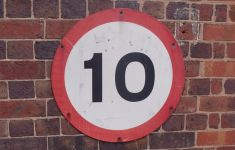 "sign reads ""10"" on brick wall"