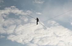 tightrope walker against cloudy sky