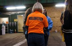 back of woman wearing orange shirt says VOLUNTEER