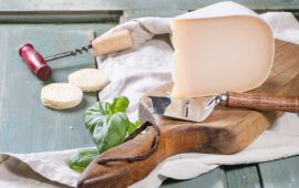 Wedge of cheese on cutting board with herbs and corkscrew