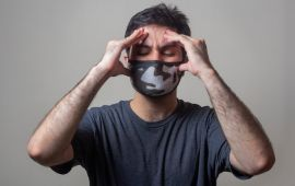 Man in facemask holds his temples demonstrating a headache