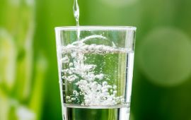 Glass of water being poured in front of green background.
